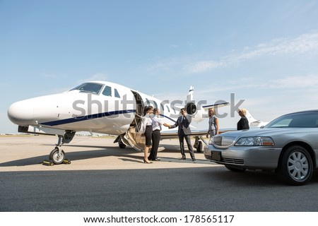 Corporate people greeting airhostess and pilot near private jet and limo at airport terminal - stock photo