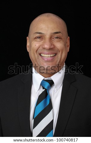 Corporate portrait of a smart intelligent businessman wearing black suit with blue striped tie looking serious and checking the time on his watch - stock photo