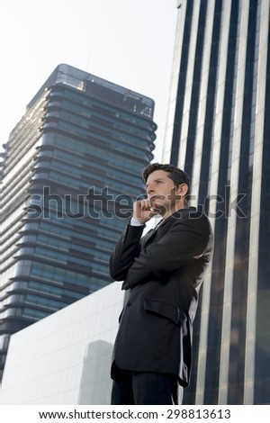corporate portrait of young attractive businessman in suit and tie looking successful and confident showing attitude standing outdoors on financial district modern background - stock photo