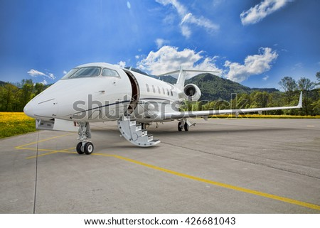 corporate private jet - plane on runway in mountains - stock photo