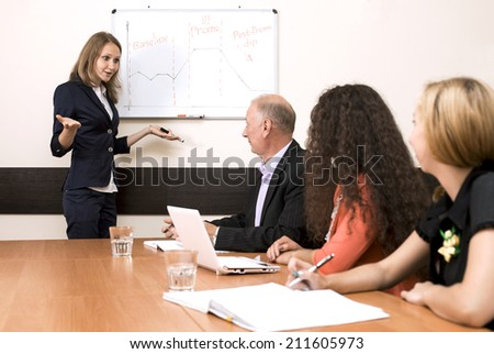 Corporate training. The female trainer is presenting the subject standing near wall chart while participants are listening - stock photo