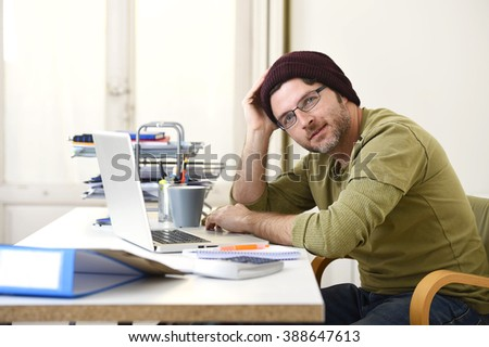 corporate young attractive hipster businessman working at home office as freelancer in casual beanie leaning on computer desk smiling happy and confident  in creative freestyle business - stock photo