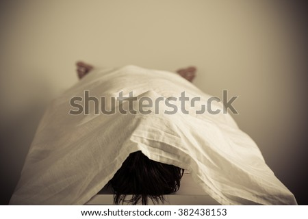 Corpse of a Person Lying on the Table Inside a Morgue with White Cloth Cover. - stock photo
