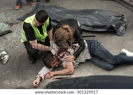 Corpse of young man lying on the street - stock photo