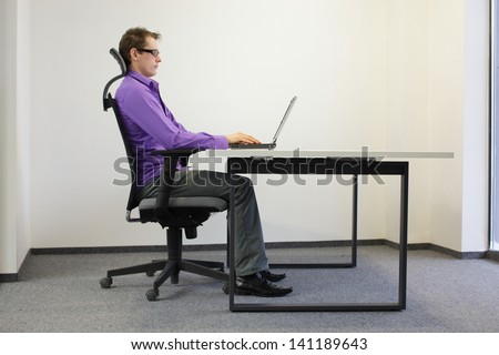 correct sitting position at workstation. man on chair working with laptop - stock photo