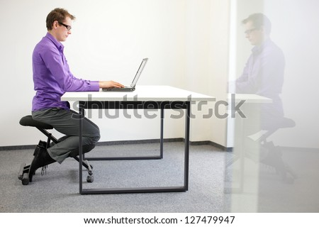 correct sitting position at workstation. man on kneeling chair - stock photo