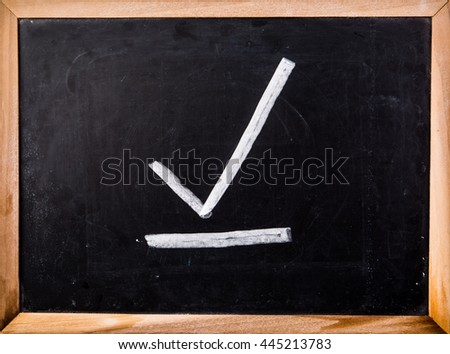correct symbol on blackboard - stock photo