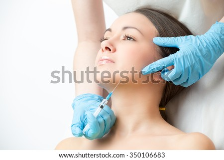 correcting injection in the chin of young woman face - stock photo