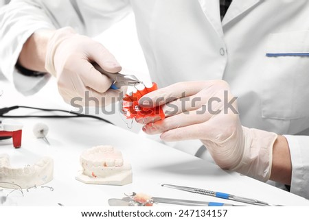 Correction of malocclusion, orthodontics.Prosthetics hands while working on orthodontic appliance  - stock photo
