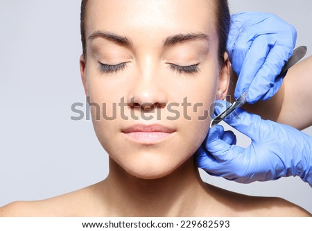 Correction of protruding ears.Caucasian woman during surgery using a scalpel - stock photo