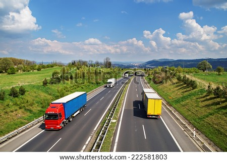 Corridor highway with the transition for animals, the highway ride colored and white trucks, in the background the city and forested mountains, view from above - stock photo