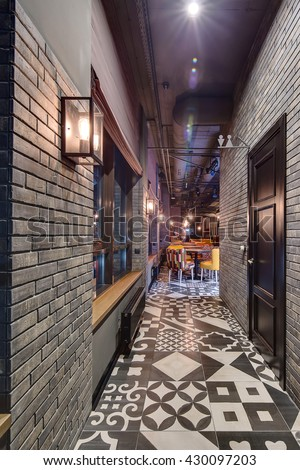Corridor with brick walls to the room in a restaurant in a loft style. On the left wall there windows with curtains, glowing glass lamps, black radiators. On the right wall there is a black door into - stock photo