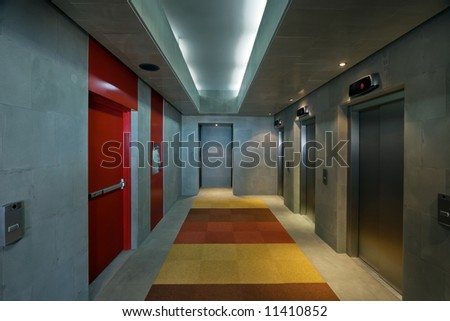Corridor with elevator and fire escape doors in a modern office environment - stock photo