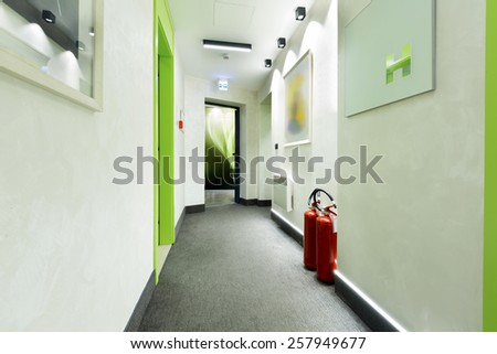 Corridor with fire extinguishers - stock photo