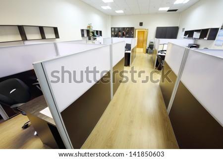 Corridor with wooden floor and empty working areas with desktops in office. - stock photo