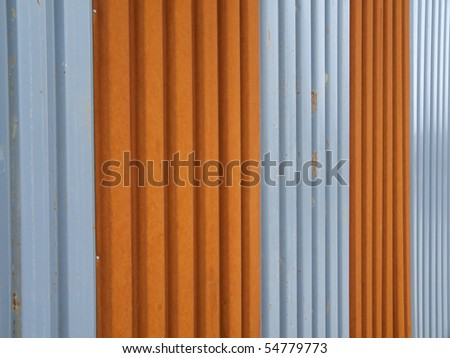 corrugated metal fence painted in orange and silver - stock photo