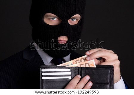 corruption concept - man in business suit and black mask holding leather purse with money - stock photo