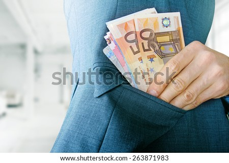 corruption concept, man putting money in jacket pocket - stock photo