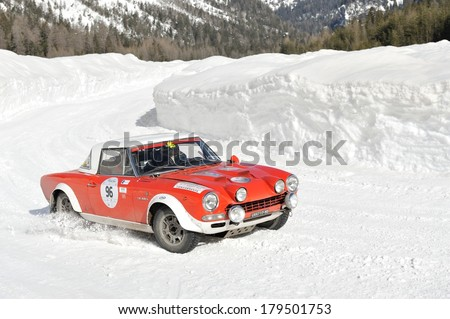 CORTINA D'AMPEZZO, ITALY - FEBRUARY 21: A red and white FIAT Abarth 124 takes part to the WinteRace classic car race on February 21, 2014 in Cortina d'Ampezzo. This car was built in 1974. - stock photo