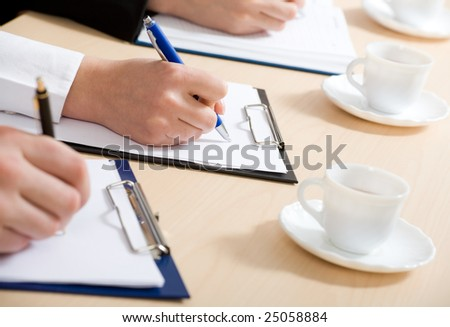 Cose-up. Hands taking notes. - stock photo