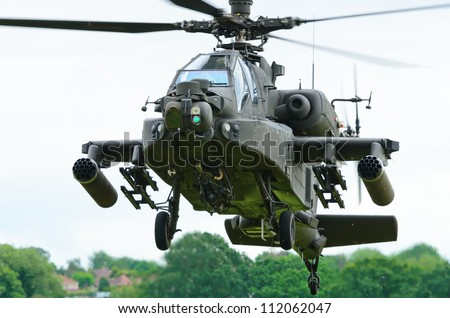 COSFORD, SHROPSHIRE, ENGLAND - JUNE 17: Boeing AH-64 Apache attack helicopter taking off for display at RAF Cosford Airshow on June 17, 2012 in Cosford, Shropshire, England. - stock photo