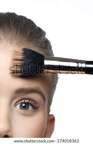 Cosmetic blusher, applying powder make up on a face with brush - stock photo
