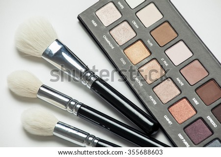 Cosmetic brushes and shadows, white background - stock photo