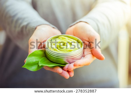 Cosmetic cream container with green herbal leaves in woman hands - stock photo
