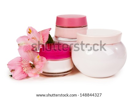 Cosmetic cream for make-up and fresh flowers isolated on white background - stock photo