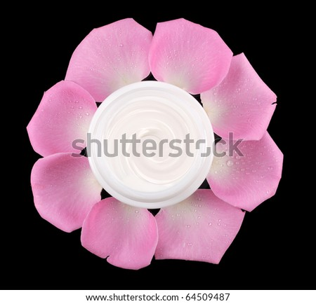 cosmetic face cream on a black background with rose petals - stock photo