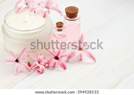 Cosmetic facial cream, bottles with aroma oil, hyacinth flowers. Natural beauty treatment. - stock photo