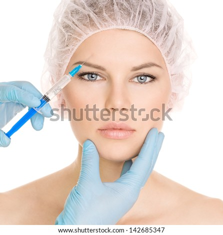 Cosmetic injection in brow zone, isolated on white background. Young pretty blue eyed female in medical cap. - stock photo