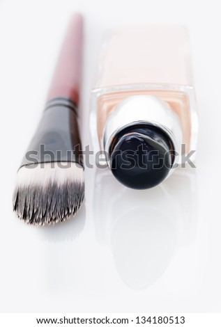 Cosmetic liquid foundation and brush on white background - stock photo