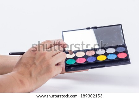 Cosmetic palettes and brushes isolated on white - stock photo