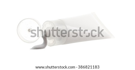 Cosmetic plastic tube with spilled cream isolated on white background - stock photo