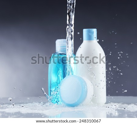 Cosmetic products in water splashes on gray background - stock photo