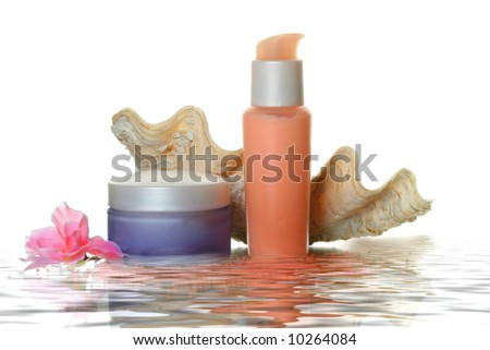 Cosmetic set: lotion bottles with cream, salt and flower in water - stock photo