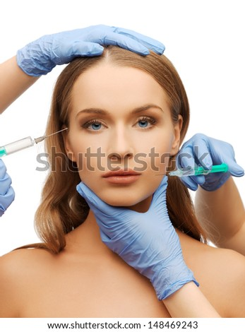 cosmetic surgery concept - woman face and beautician hands with syringes - stock photo