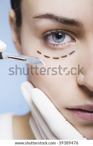 cosmetic surgery with scalpel on a young woman - stock photo