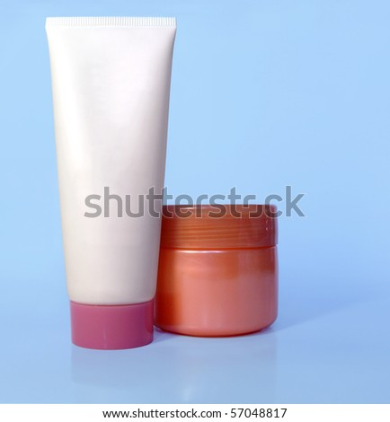 Cosmetic tube and pot of cream on light blue background, blank for applying new branding. - stock photo