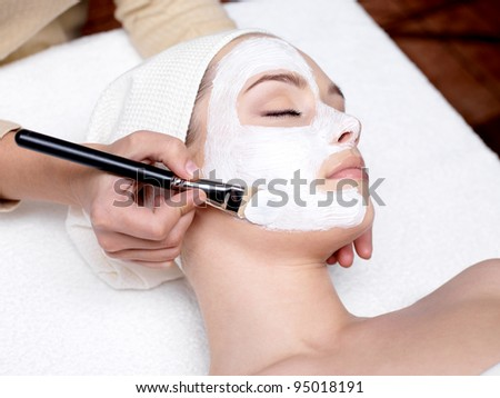 Cosmetician applying facial beauty mask for young beautiful woman at spa salon - stock photo