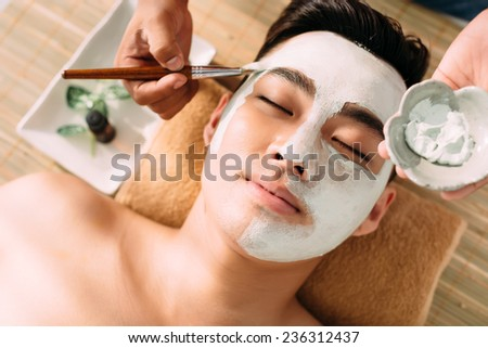 Cosmetician applying mask to the face of young handsome man - stock photo