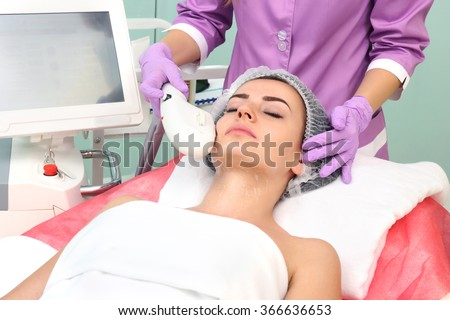 Cosmetician perfiming photo rejuvenation cosmetology procedure for a woman - stock photo