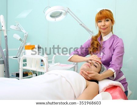 Cosmetician working in beauty parlour. She doing facial massage with accent on the neck - stock photo