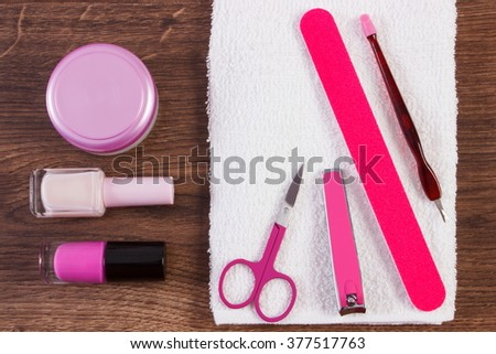 Cosmetics and accessories for manicure or pedicure, nail file, nail polish and remover, scissors, nail clippers, fluffy towel, concept of nail care - stock photo