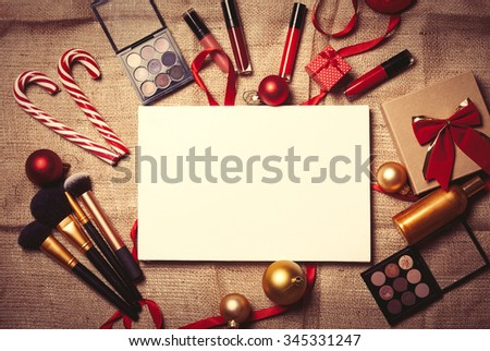 Cosmetics and christmas gifts on jute background - stock photo