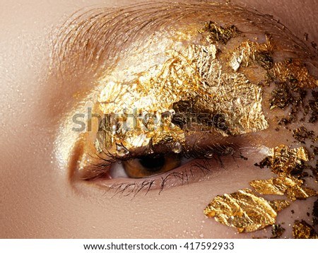 Cosmetics and make-up. Closeup macro shot of fashion sparcle visage. Closeup portrait of beautiful young woman with golden foil on face. Creative makeup. - stock photo