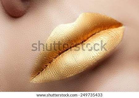 Cosmetics and make-up. Shoot of a beautiful girl with golden lips lipstick and gloss. Sexy and stylish lips. Lips against the backdrop of smooth skin. Fashion golden lips closeup located diagonally - stock photo