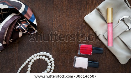 Cosmetics and women's accessories on wooden background. Clutch, pearl, shawl and red nail polish - stock photo