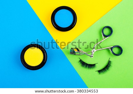 cosmetics for makeup. bright blue background with green eyelashes glamorous and trendy - stock photo